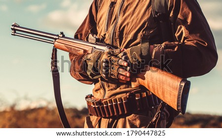 Hunting period. Male with a gun. Hunter with a backpack and a hunting gun. Hunter man. A hunter with a hunting gun and hunting form to hunt. The man is on the hunt. #1790447825