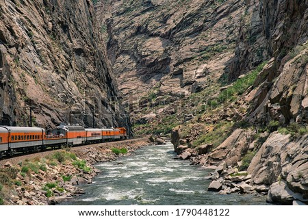 Train riding deep in the royal gorge beside the arkansas river in Colorado. Orange engine beside rushing blue water with rocky cliffs all around Royalty-Free Stock Photo #1790448122
