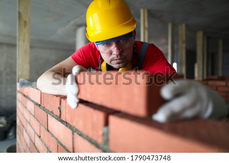 Builder carefully puts red brick on the masonry. Quick work bricklayer. Guy measures level masonry. Man is building brick wall. Correctly calculate material. Builder manually carries brick structure #1790473748