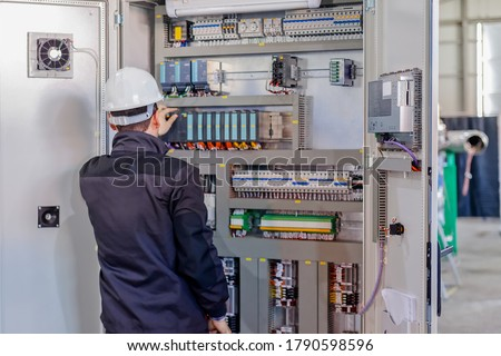 Man worker checking advanced industrial control panel; note shallow depth of field Royalty-Free Stock Photo #1790598596