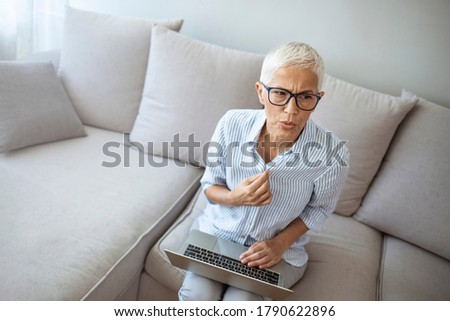 Gradual process.Beautiful mature woman touching shirt and having hot flash. Exhausted mature woman entering menopause. Portrait of an attractive senior woman sitting on a sofa at home with a hot flash Royalty-Free Stock Photo #1790622896