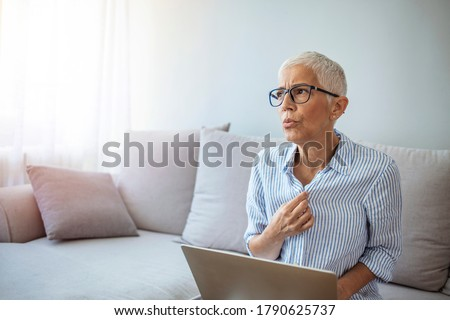 Mature Woman Experiencing Hot Flush From Menopause. Tired mature woman tolerating hot flash. Hot flashes. Exhausted mature woman resting on sofa and having hot flash Royalty-Free Stock Photo #1790625737