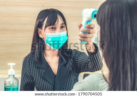 Receptionist and guest wearing face mask at front desk while having conversation in office or hospital . Covid 19 and coronavirus infection protection and protective policy concept . Royalty-Free Stock Photo #1790704505