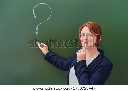 Teacher drew a question mark in chalk on a blackboard, copy space on green background. Woman teacher with a sad face at the school blackboard.