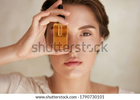 Beauty Face. Close Up Portrait Of Woman With Bottle Of Essential Oil. Beautiful Model With Radiant And Glowing Facial Skin Looking At Camera. Moisturizing With Serum Collagen And Hyaluronic Acid. Royalty-Free Stock Photo #1790730101