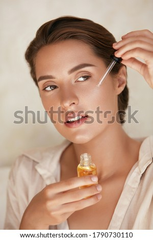 Beauty Face. Woman Applying Essential Oil On Facial Skin And Looking Away. Beautiful Model Moisturizing Derma With Natural Vitamin E, Serum Collagen And Hyaluronic Acid. Royalty-Free Stock Photo #1790730110