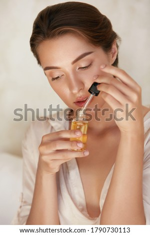 Beauty. Woman With Bottle Of Essential Oil For Glowing And Hydrated Face Skin. Facial Treatment With Serum Collagen, Hyaluronic Acid And Natural Vitamin E For Anti-Aging Therapy.  Royalty-Free Stock Photo #1790730113