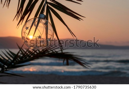 Christmas decorations glass ball during sunset on palm twig over the sea. Ocean beach - Christmas and New Year holidays in hot countries concept. Congratulations, card. Copy space
