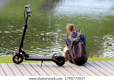 Tourist guy is resting on the lake coast and taking pictures of ducks in between a ride on an electric scooter