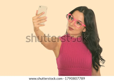 Studio shot of young beautiful Spanish woman taking selfie picture with mobile phone
