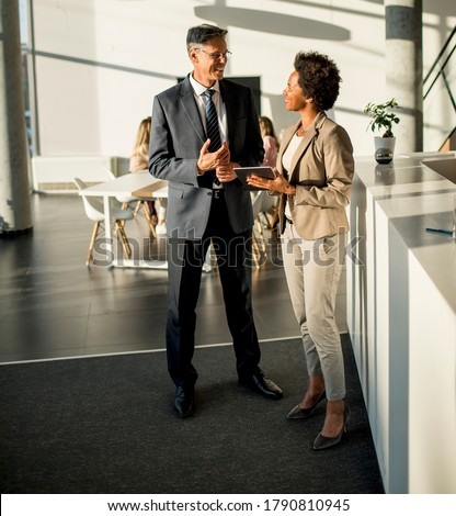 Multiethnic business people using digital tablet while standing in the modern office Royalty-Free Stock Photo #1790810945