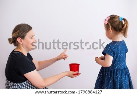 Side view of woman scolding little girl for painting walls in modern apartment