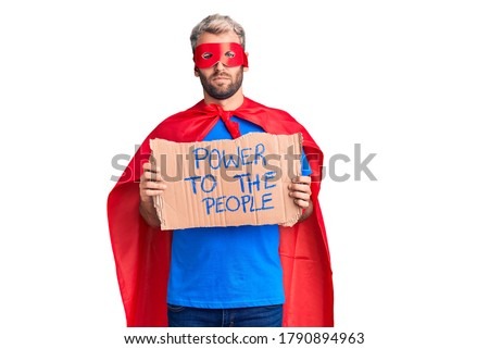 Young blond man wearing super hero custome holding power to the people cardboard banner thinking attitude and sober expression looking self confident