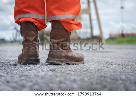 Close-up at Oil field operator's safety boots part with background of outdoor site location. Working in dangerous industrial or business concept action photo.