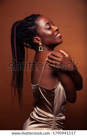 pretty young african american woman with braids posing cheerful gesturing on brown background, lifestyle people concept #1790941517