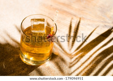 Whisky liqueur glass with ice cubes on the sandy beach #179096951