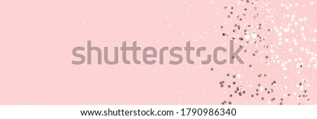 Silver stars confetti on a pink pastel background. Holidays banner with place for text. Royalty-Free Stock Photo #1790986340