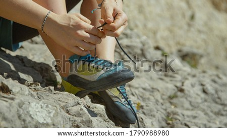 CLOSE UP, DOF: Unrecognizable woman ties her climbing shoes before climbing a difficult boulder. Athletic woman on rock climbing trip gets ready for her first ascent by tying her climbing shoes. #1790988980