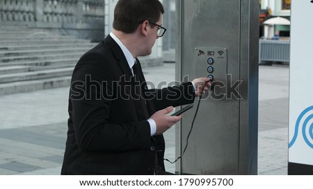 Confident businessman in black formal suit at bus stop puts phone on charge and talks on it. New technologies for charging phones at city stops in town center. #1790995700