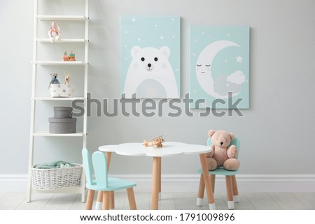 Children's room interior with table and cute pictures on wall