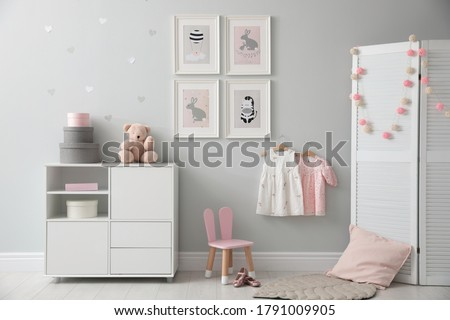 Stylish baby room interior with chest of drawers and cute pictures on wall