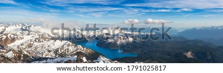 Aerial Panoramic View of Garibaldi surrounded by Beautiful Canadian Mountain Landscape during a sunny and cloudy day. Taken near Squamish and Whistler, North of Vancouver, British Columbia, Canada. Royalty-Free Stock Photo #1791025817