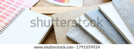 On table is color scheme and samples with color. Selection color laminate and ceramic tiles for repairs kitchen. Color combination in apartment. Coordination choice finishing materials with customer Royalty-Free Stock Photo #1791059924