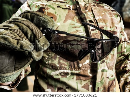 Photo of soldier in military multicam shirt and gloves holding tactical glasses side view.