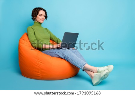 Full body profile side photo of focused ceo worker sit bean chair use laptop search information wear green casual style sweater isolated blue color background