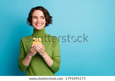 Portrait of positive cheerful girl use smart phone look copyspace share social media news wear style stylish trendy jumper isolated over blue color background #1791095171