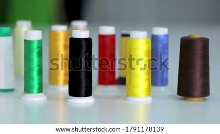 A photo of multicolored spools of sewing thread on a white background #1791178139