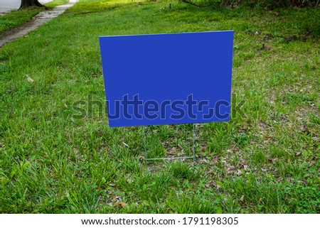 Blank dark blue sign on a green grass lawn on metal stand