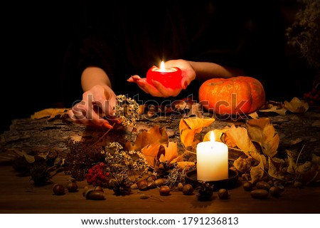Forest witch at work on the altar. Female hands with sharp red nails among candles, herbs, pumpkin, nuts, dry leaves, ashberry, selected focus, low key. Halloween, Samhain night, autumn, magic Royalty-Free Stock Photo #1791236813