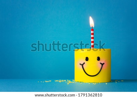 Yellow happy face birthday cake with one candle Royalty-Free Stock Photo #1791362810