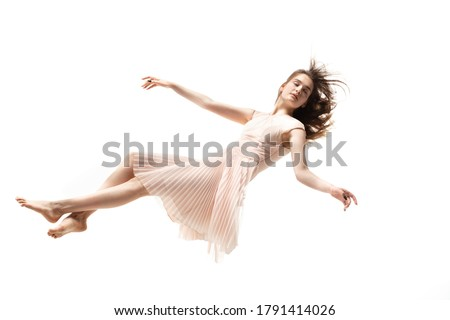 Mid-air beauty cought in moment. Full length shot of attractive young woman hovering in air and keeping eyes closed. Levitating in free falling, lack of gravity. Freedom, emotions, artwork concept. Royalty-Free Stock Photo #1791414026