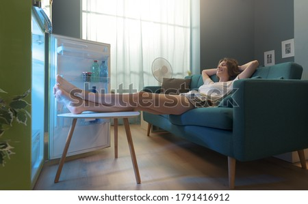 Happy woman lying on the sofa at home and cooling herself in front of the open fridge Royalty-Free Stock Photo #1791416912