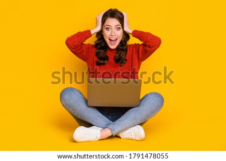 Portrait of her she nice attractive amazed cheerful cheery lucky wavy-haired girl sitting using laptop lucky news lottery win isolated on bright vivid shine vibrant yellow color background