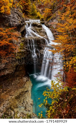 Autumn mountain waterfall vertical view. Mountain forest waterfall in autumn. Autumn waterfall in autumnal mountain forest. Autumn waterfall in mountains #1791489929