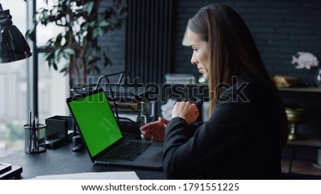 Business woman calling video on laptop computer with green screen in office. Female entrepreneur having video conference online at remote workplace. Businesswoman gesturing during video conversation