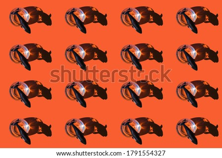 Ironic conceptual pattern of a whale coming out of a circular fish tank on an orange background