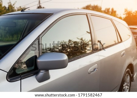 Front view of a Japanese car Honda in the body of a hatchback of the side of a silver station wagon in a parking lot with green trees after being washed ready for sale. Royalty-Free Stock Photo #1791582467
