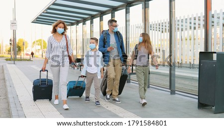 Caucasian happy family with two cute small kids walking at bus stop or train station, carrying suitcases on wheels and talking. Parents with little daughter and son in medical masks travelling. Royalty-Free Stock Photo #1791584801