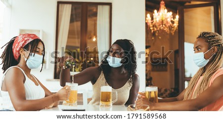 Three young African American girlfriends sitting at brewery (pub) with beer glasses wearing surgical masks. 3 Black girls are drinking ale in a luxury bar o restaurant. Pouring beer to friend concept. #1791589568