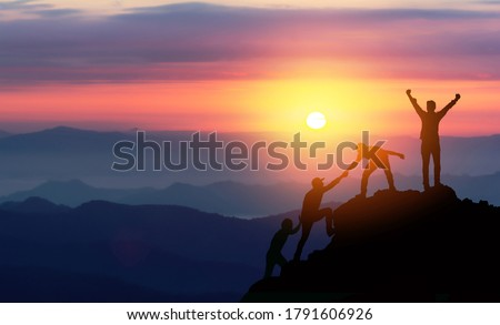 Teamwork helping hand trust assistance silhouette in mountains, sunset. Team of climbers man hiker, help each other on top of mountain, Business concept. Royalty-Free Stock Photo #1791606926