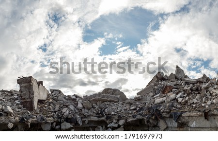 A pile of concrete gray debris of a destroyed building with a huge beam in the foreground against a blue sky with clouds. Panorama. Royalty-Free Stock Photo #1791697973