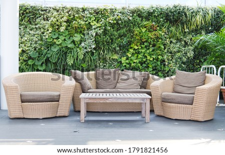 Luxury brown rattan patio garden and hotel furniture chairs and table with the earth-tone pillow set on it and green bush background for recreational, relaxation and resting.  Royalty-Free Stock Photo #1791821456