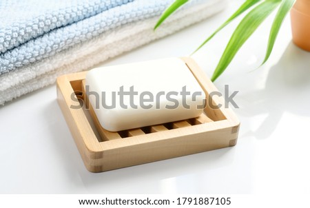 White Soap bar on wooden soap dish and cotton towels on white counter table in the bathroom. Royalty-Free Stock Photo #1791887105