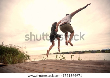 caucasian couple jumping together in the river holding hands Royalty-Free Stock Photo #1791894971