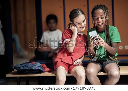The little teammates enjoy the content from the cell phone in the locker room Royalty-Free Stock Photo #1791898973