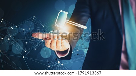 Businessman hand holding hammer icon,with futuristic line network, concept bid winner highest bidder in final lift,with public sale property auctioned business competition,e-auction and online bidding #1791913367